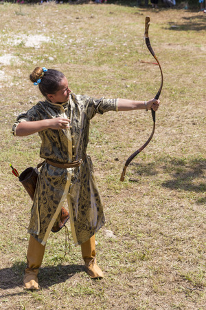 ASENVOGRAD, BULGARIA - JUNE 25, 2016 - Medieval fair in Asenovgrad recreating the life of Bulgarians during the Middle ages. Girl in a costume shooting arrows at a target.