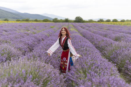 bulgaria girl: Woman dressed in traditional bulgarian dress called Nosia jumping in a lavender field.