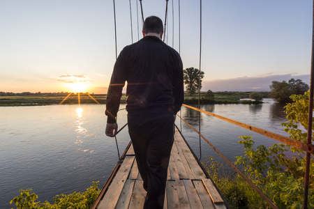 bridge in nature: Man walking on an old suspension bridge towards the sunset.