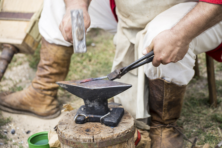 envelop: Blacksmith making a small envelop opener knife. Stock Photo