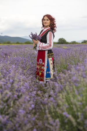 bulgaria girl: Woman dressed in traditional bulgarian dress called Nosia enjoying a walk in a lavender field.
