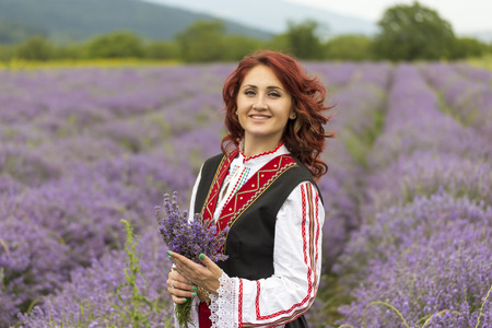 Vrouw, gekleed in traditionele Bulgaarse kleding genoemd Nosia genieten van een wandeling in een veld lavendel.