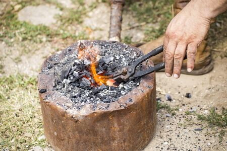 forge: Blacksmith melting a piece of metal in a small forge. Stock Photo