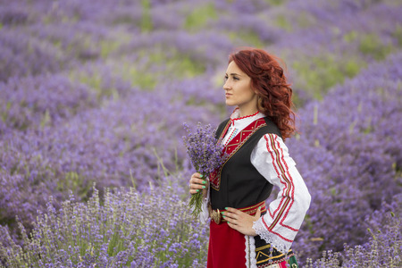 Woman dressed in traditional bulgarian dress called Nosia enjoying a walk in a lavender field.
