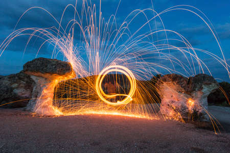 steel wool: Spinning a lit steel wool between rocks. The circle looks like a portal to another dimension. Stock Photo