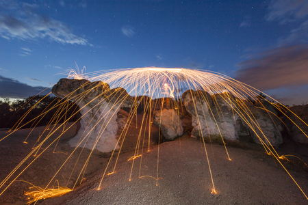 rock wool: Steel wool spining on a rock. The sparks are creating a shower effect.