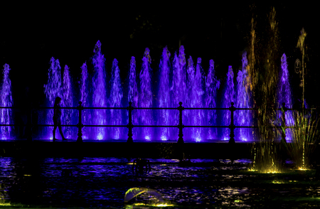 Silhouette of a child looking at a colorfully lit fountain
