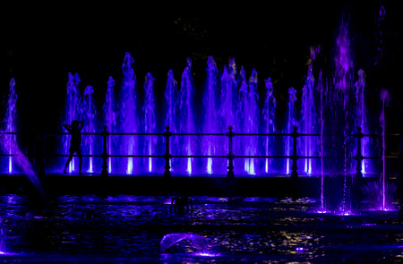 colorfully: Silhouette of a child looking at a colorfully lit fountain