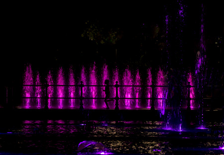 colorfully: Silhouette of a child running through colorfully lit fountain