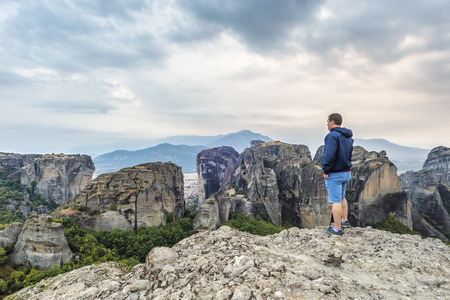 Man ot the edge of a cliff looking at the magnificent vew of Meteora rock formations