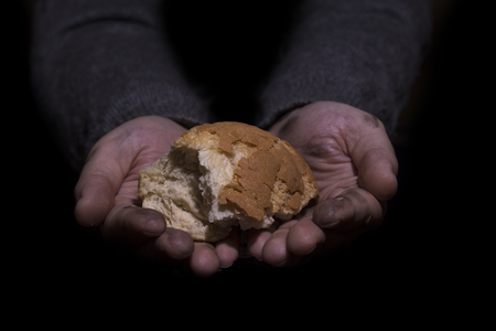 hunger: Poverty concept. Dirty hands giving bread isolated on balck background.
