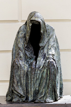 Scarry faceless statue wearin a cloack.