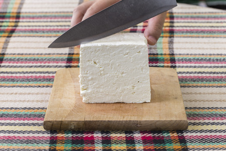 Cutting traditional bulgarian salty white cheese with a knife. First person point of view concept. Stockfoto