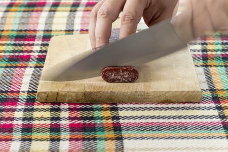 Cutting traditional Bulgarian flat sausage called lukanka Stock Photo