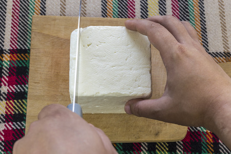 Cutting traditional bulgarian salty white cheese with a knife. First person point of view concept. Stock Photo