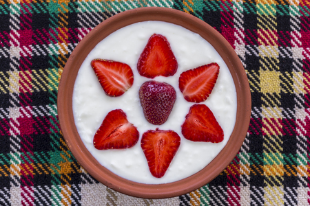 Strawberries sliced and beautifully arranged in a bowl of yogurt.
