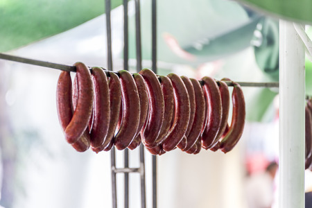 Many sausages hangin on a wooden stick