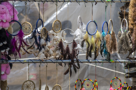 Many small and colorful dreamcatchers hanging from a pole