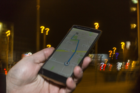 Lost in the city concept. Hand holding phone with map on the screen and question mark bokeh in the background 免版税图像