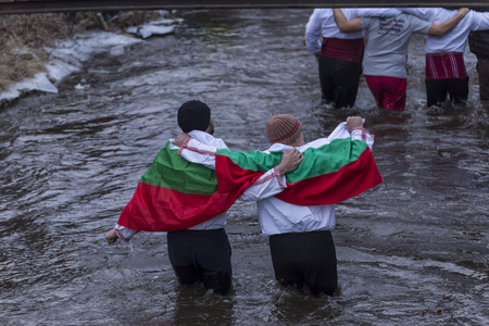 KALOFER, BULGARIA - JANUARY 06, 2019 - Traditional Bulgarian horo dance in the cold icy waters of Tundzha river in Kalofer city Bulgaria.