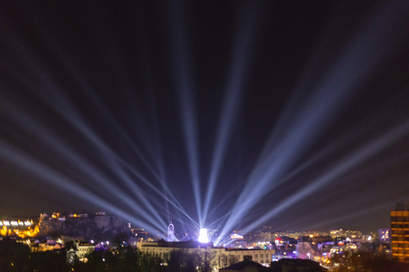 Alien spaceship landing in a city enviroment. UFO concept with bright light beams in the sky. Stock Photo