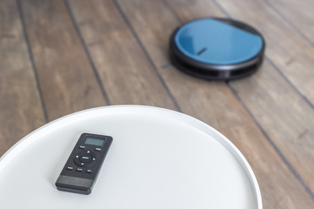 Robot vacuum cleaner remote laying on a white coffee table