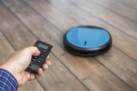 Man holding a remote and controling a robot vacuum cleaner
