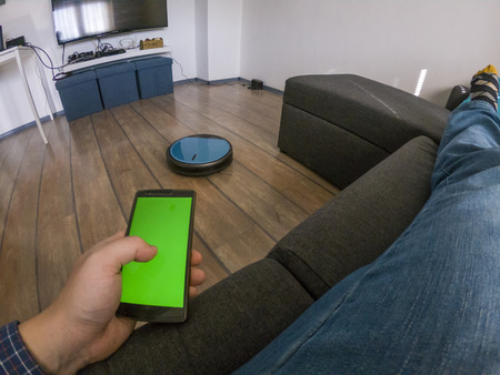 Man laying on a couch holding a smartphone and controlling a robot vacuum cleaner through an app