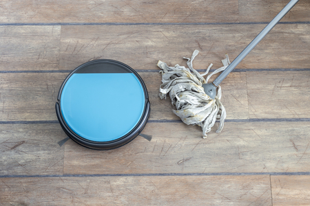 Old versus new and technology evolution concepts. Robot vacuum cleaner and mop side by side. Stock Photo