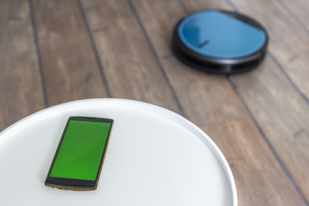 Robot vacuum cleaner control app on a smartphone laying on a white coffee table