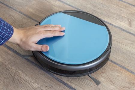 Hand petting a robot vacuum cleaner. Pet behavior concept.