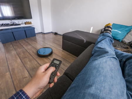 Man laying on a couch holding a remote control for a robot vacuum cleaner