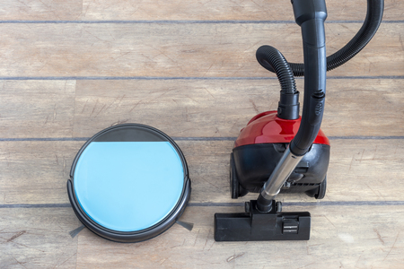 Old versus new and technology evolution concepts. Robot and regular vacuum cleaners side by side.