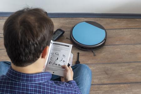 Mann sitzt auf dem Boden und liest die Bedienungsanleitung für einen Roboterstaubsauger