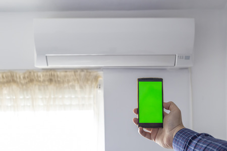 Air conditioner smartphone remote control concept. Hand holding a phone with green screen in front of ac unit.