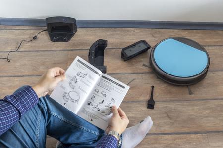 Homme assis sur le sol et lisant le manuel d'instructions d'un aspirateur robot