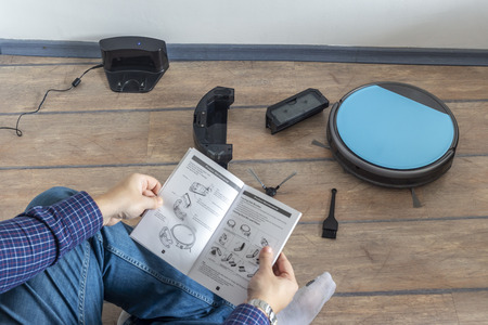 Man sitting on the floor and reading instructions manual for a robot vacuum cleaner