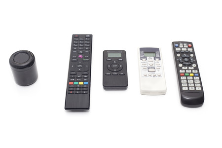 Universal ir and wifi remote with voice activation next to old fashioned remotes with buttons isolated on white background. Reklamní fotografie