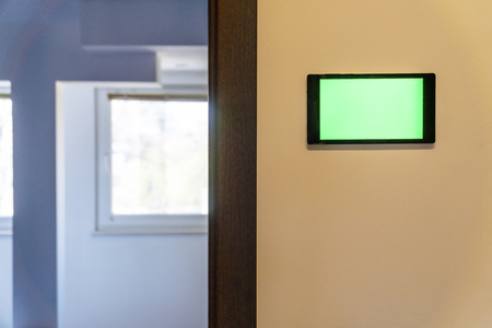 Home automation concept. Device with blank screen hanging on a wall.