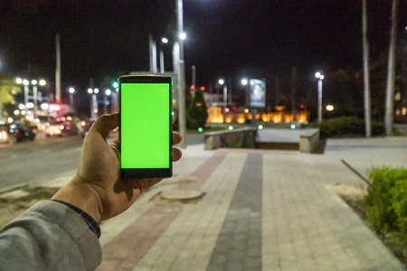 Home automation and smart home concept. Human nad holding a smartphone on the street at night and adjusting the home temperature from an app.