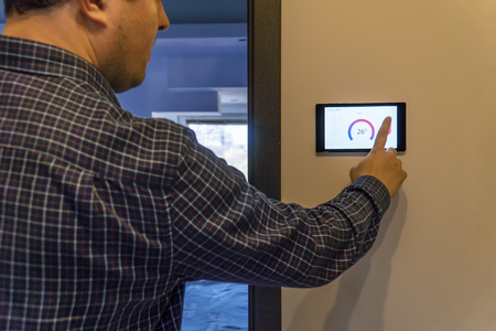 Smart home control and security concept. Person adjusting the temperature by pressing buttons on a device screen.