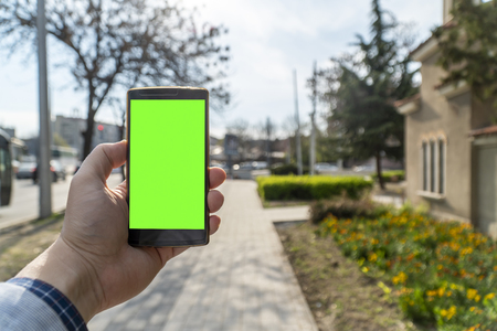 Person holding smartphone with blank screen with city streets in the background