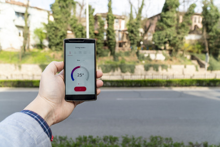 Home automation and smart home concept. Human nad holding a smartphone on the street and adjusting the home temperature from an app.