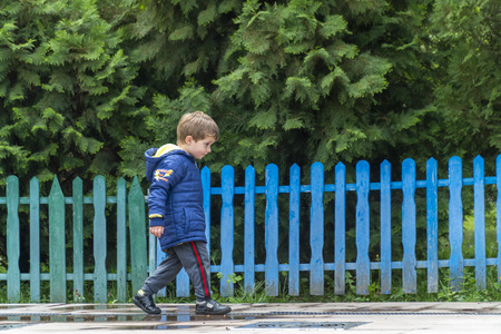 Yound boy walking around in a park with his head down with a colorful fence in the background Banque d'images - 122311002