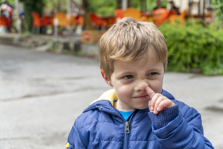Young boy beeing funny and picking his nose at outdoors park 免版税图像