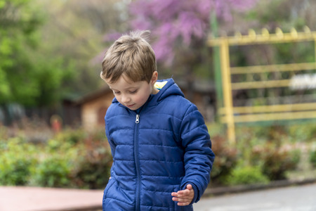 Young boy walking around in a outdoors park Foto de archivo