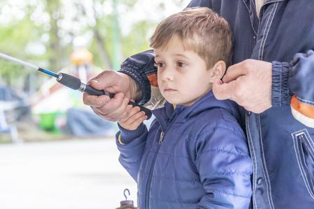 使用捉住橡胶鸭子的年轻男孩在室外游乐园。他的祖父帮助他。