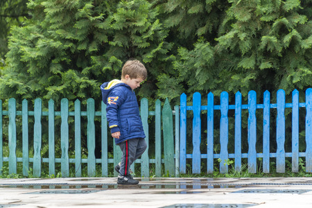 Yound boy walking around in a park with his head down with a colorful fence in the background Banque d'images - 122312450