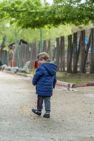 Young boy walking in a park and looking back over his shoulder