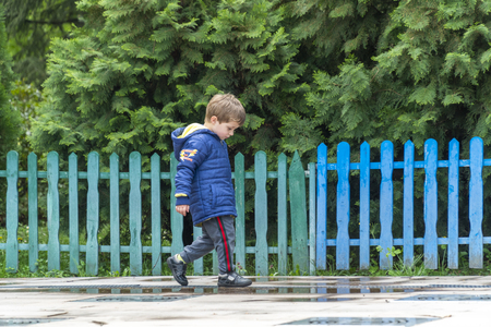 Yound boy walking around in a park with his head down with a colorful fence in the background Banque d'images - 122314853